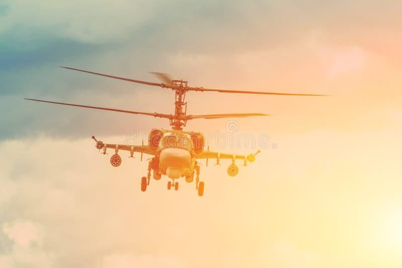 Den militära stridhelikoptern flyger hängningar i luften royaltyfria foton