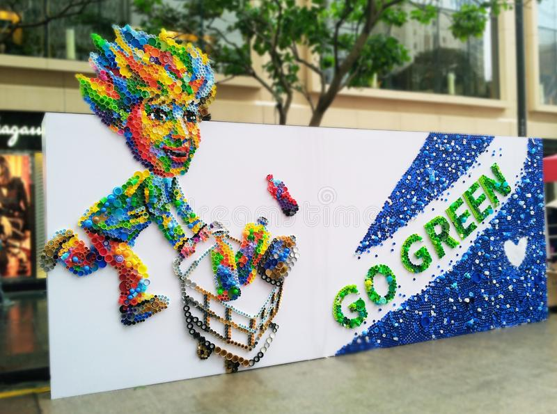 Den miljö- vänskapsmatchen går grön med plast- lock som upcycling nya konstskapelser royaltyfri fotografi