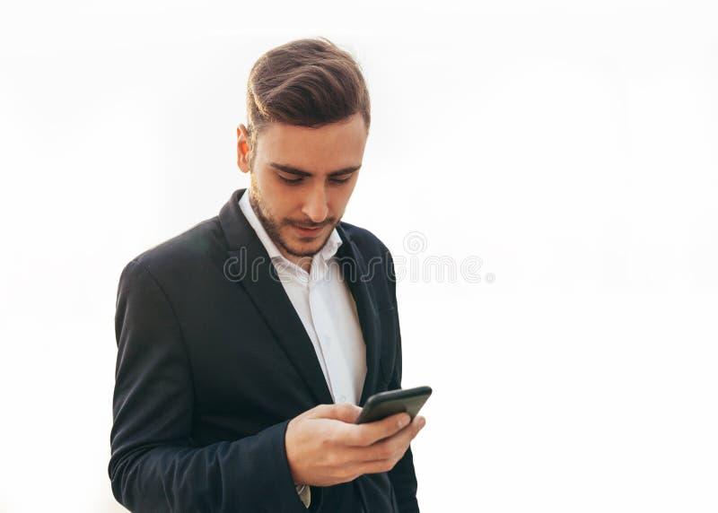 Den Millennial affärsmannen ser in i skärmen av hans mobiltelefon Det lyckliga ung flickainnehav hänger lös på en vitbakgrund Ung royaltyfri fotografi