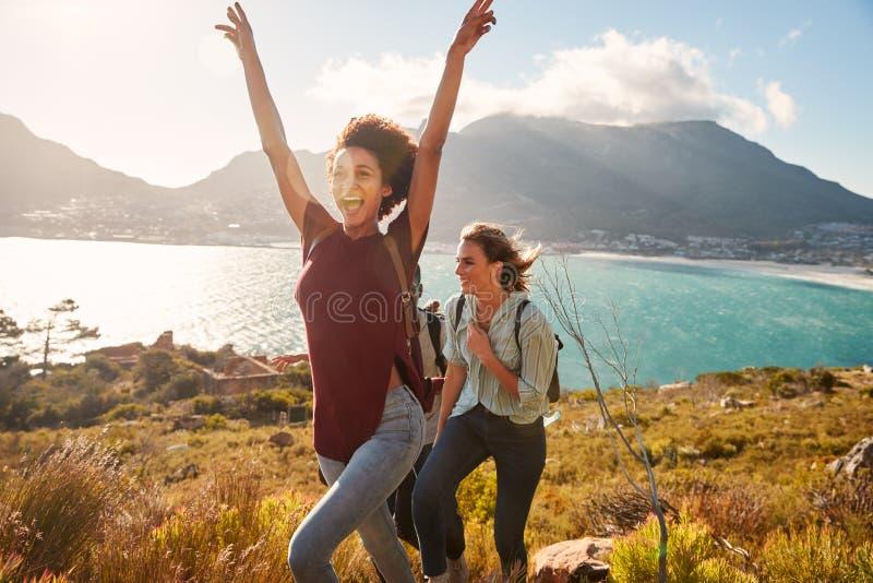Den Millennial afrikansk amerikankvinnan som fotvandrar vid kusten med en vän, firar nå toppmötet royaltyfri fotografi