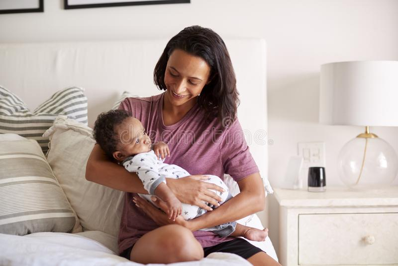 Den Millennial afrikansk amerikanmodern som sitter på hennes säng som rymmer hennes tre månad gammal, behandla som ett barn sonen royaltyfri bild