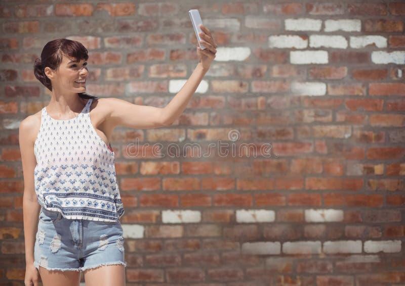Den Millennial flickan i sommar beklär att ta selfie mot väggen för röd tegelsten royaltyfri foto