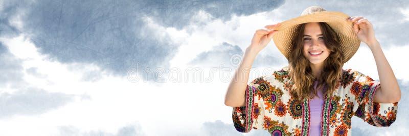 Den Millennial kvinnan i sommar beklär den hållande hatten mot molnig himmel arkivbilder