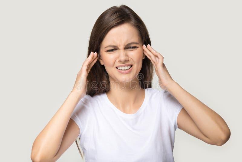 Den Millennial kvinnan som trycker på tempel, lider från migränstudioskott arkivfoton