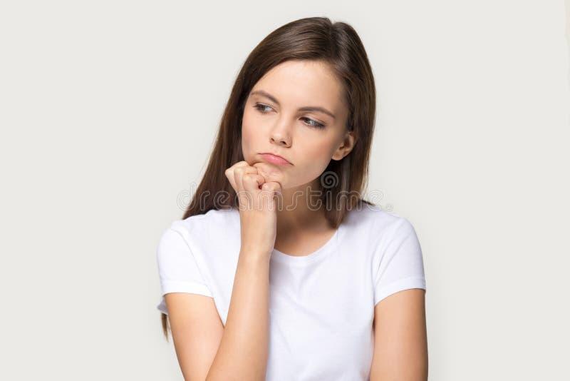 Den Millennial ledsna eftertänksamma kvinnan känner rubbning som isoleras på grå bakgrund royaltyfria foton