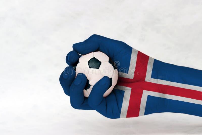 Den mini- bollen av fotboll i den Island flaggan målade handen på vit bakgrund Begrepp av sporten eller leken i handtag eller min arkivbild