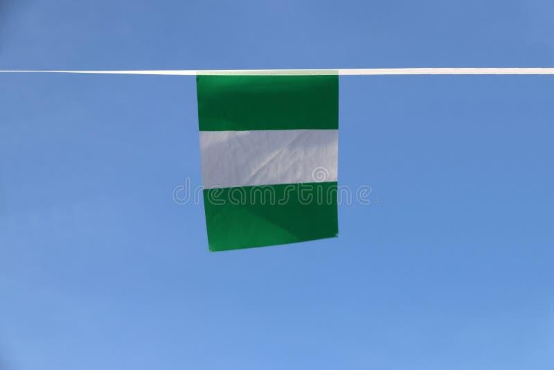 Den mini- tygstångflaggan av Nigeria, flaggan har tre vertikala musikband av gräsplan, vit, gräsplan arkivbilder
