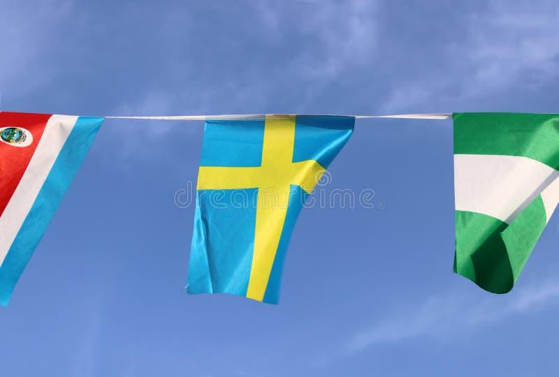 Den mini- tygstångflaggan av Sverige som den är, består av en guling eller ett guldnordbokors på ett fält av blått som hänger på  arkivfoton