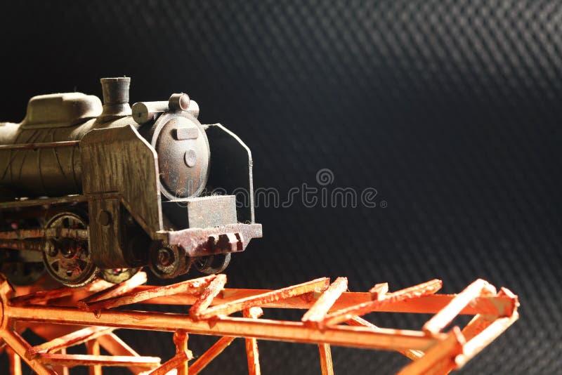 Den miniatyrplast- modelljärnvägen på bron royaltyfri foto