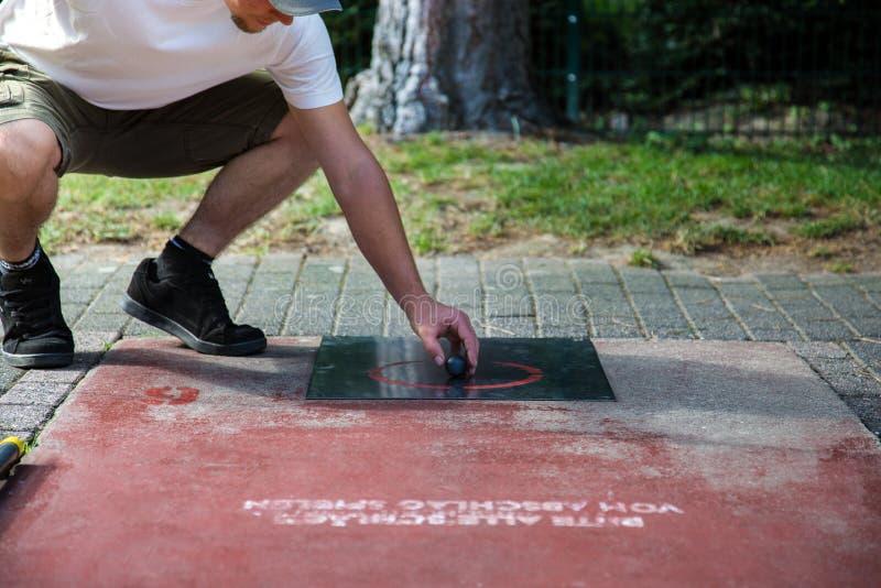 Den Minigolf spelaren kommer med stickreplikbollen in i positionen för leken royaltyfri foto