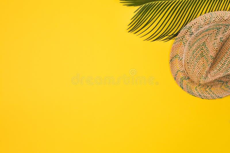 Den Minimalist sommarlägenheten lägger med, palmblad och den Panama hatten på guling royaltyfria bilder