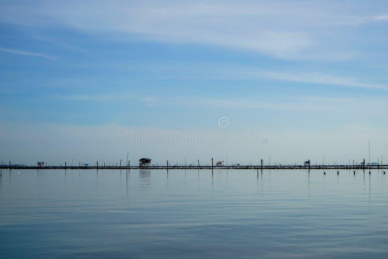 Den minsta fiskarekojan, bambu och träpinnestrukturfiskerin brukar ovanför havsvåtmark med klar himmelbakgrund arkivbild