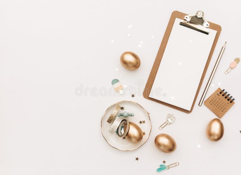 Den minsta lägenheten lägger guld- påskägg med linneförklädet och proteablomman på vit bakgrund royaltyfria bilder