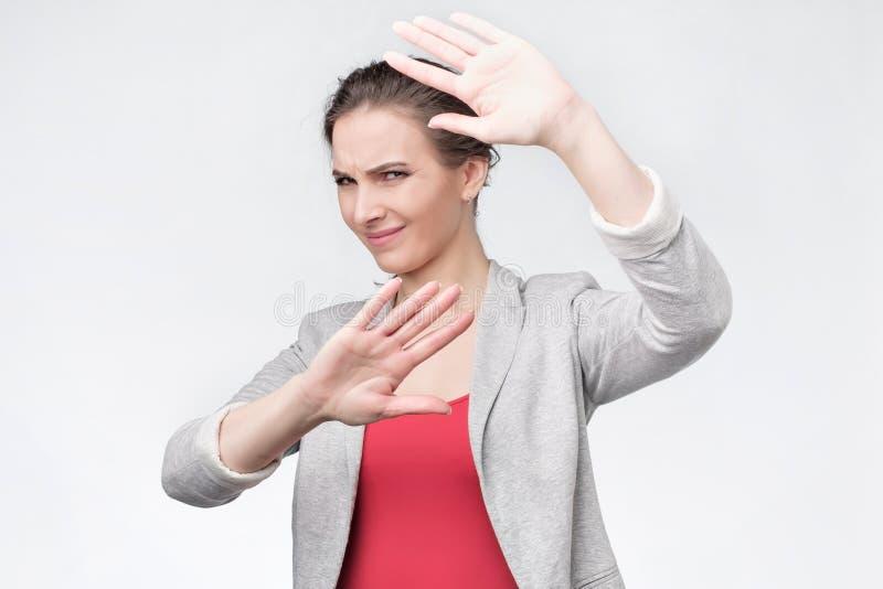 Den misshog unga kvinnan som visar två, gömma i handflatan Vägranbegrepp royaltyfria bilder