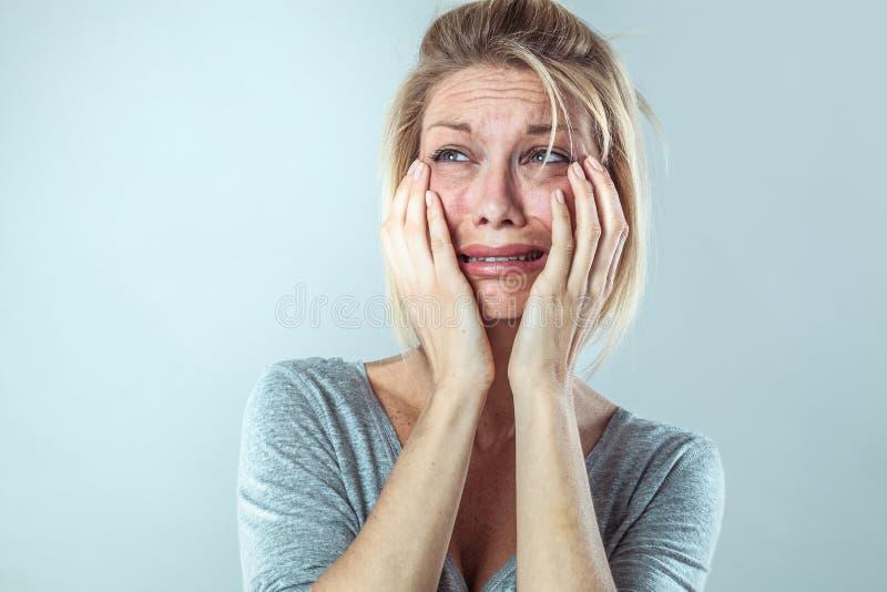 Den missmodiga unga blonda kvinnan smärtar in att uttrycka hennes sorgsenhet arkivfoto