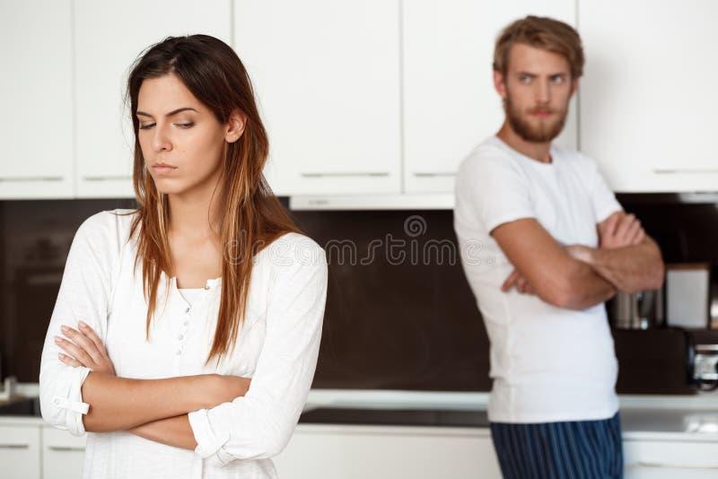 Den missnöjda härliga brunettflickan grälar in med hennes pojkvänbakgrund arkivbilder