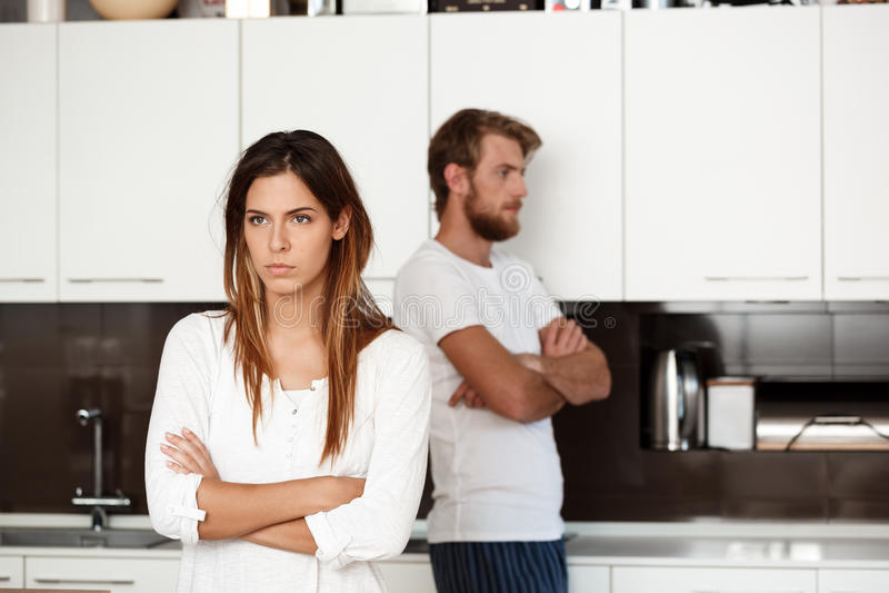 Den missnöjda härliga brunettflickan grälar in med hennes pojkvänbakgrund fotografering för bildbyråer