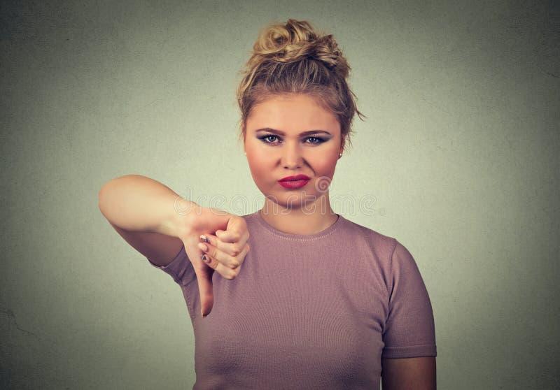 Den missnöjda ilskna skitförbannade kvinnan förargade att ge tummar gör en gest ner fotografering för bildbyråer