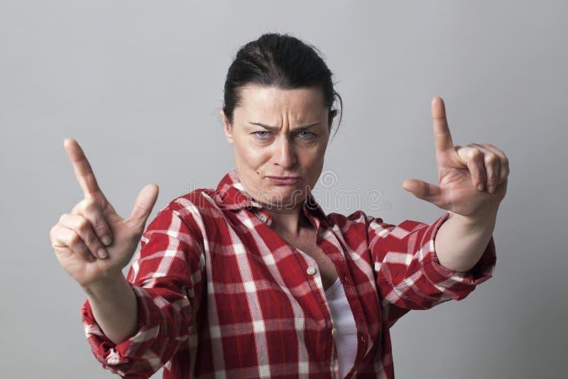 Den missnöjda mitt åldrades kvinnan som visar en aggressiv handgest royaltyfri foto