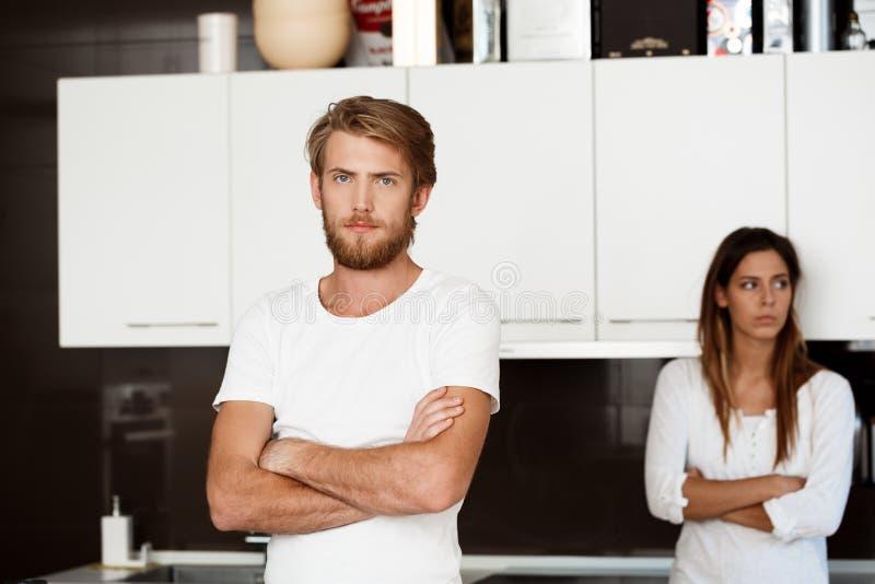 Den missnöjda stiliga mannen grälar in med hans flickvänbakgrund arkivbilder