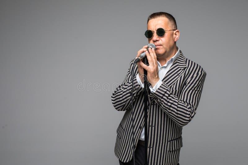 Den mitt- ålderimpressariointervjuaren med sinnesrörelser Hållande mikrofon för ung elegant mogen man mot vit bakgrund Impressari arkivbild