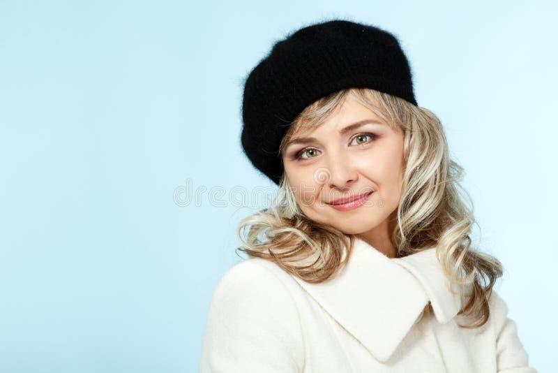 Den mitt- vuxna lyckliga attraktiva kvinnan ger en blinkning, vinterståendenolla royaltyfria foton