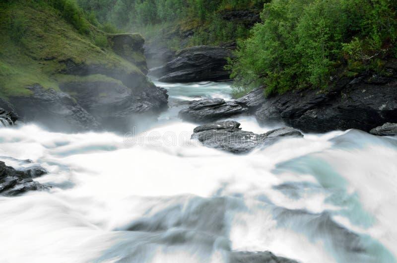 Den mjölkaktiga vita massiva långa hala dalen för vattenfallet vaggar ner och stenar i sommar royaltyfri bild