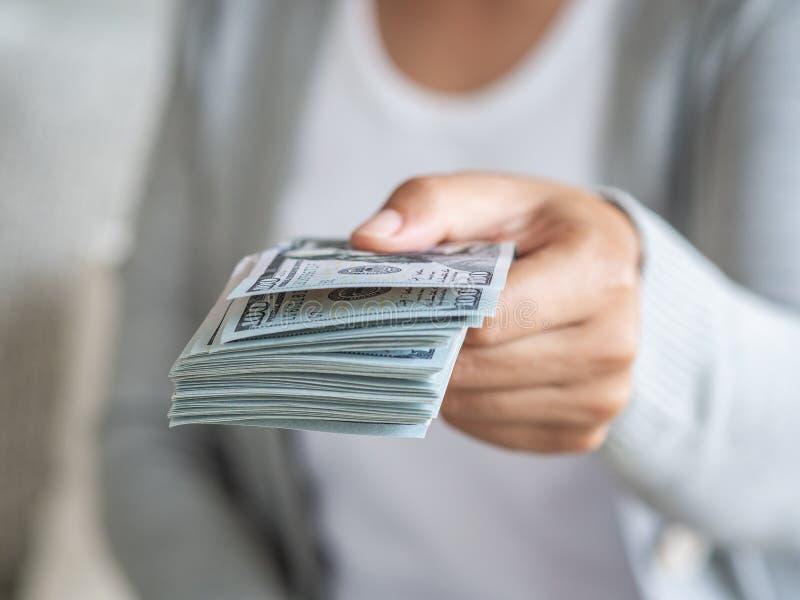 Den mjuka fokusen på kvinna räcker förslag av pengar oss dollarräkningar till dig arkivbilder
