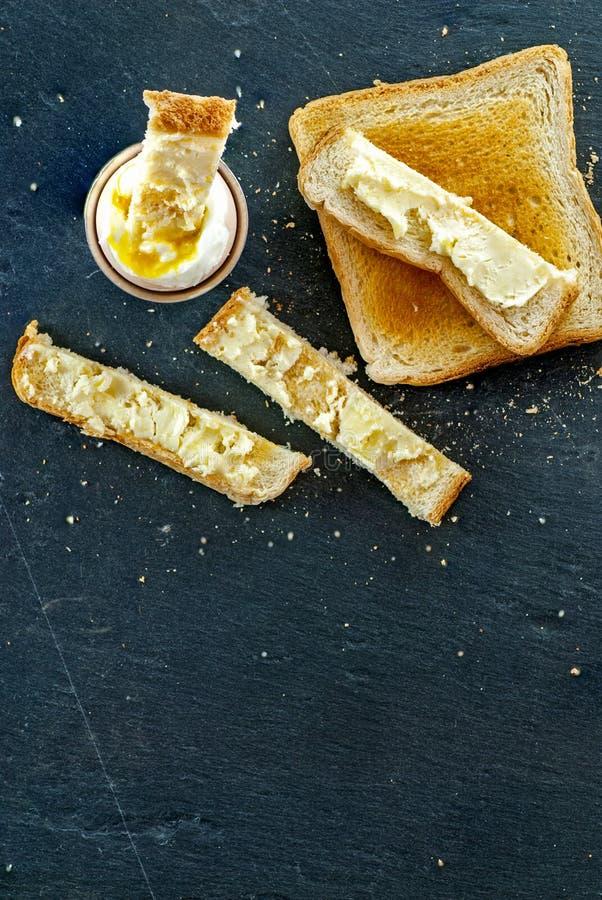 Den mjuka kokta ägg- och rostat brödbrödskivan med smör frukosterar begrepp arkivfoton