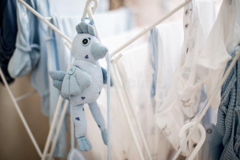 Den mjuka leksakblåttfågeln nära spädbarn behandla som ett barn tvätteriuttorkning arkivbilder