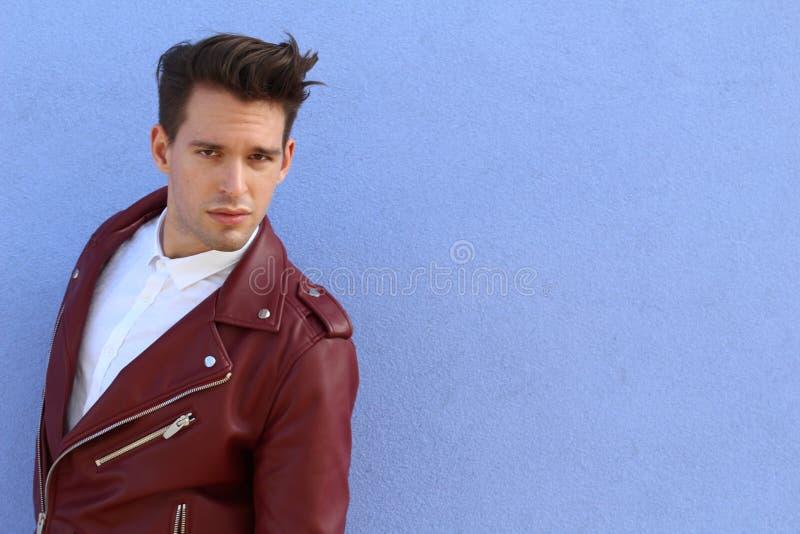 Den moderiktiga avkopplade unga mannen med ett modernt frisyranseende mot en blå bakgrund som ser kameran, tre fjärdedel, poserar arkivfoto