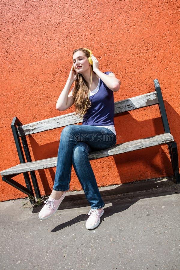 Den moderiktiga unga kvinnan som tycker om att stänga sig, synar, i att lyssna till musik arkivfoto