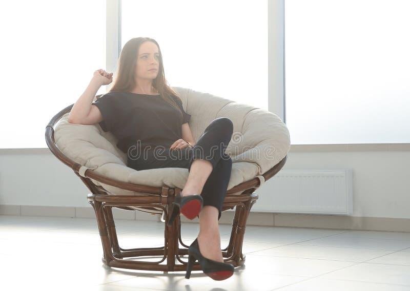 Den moderna affärskvinnan kopplar av i en bekväm stol royaltyfria foton