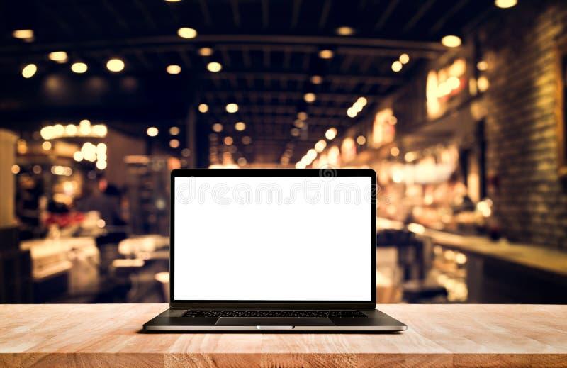 Den moderna datoren, bärbar dator med den tomma skärmen på tabellkafét shoppar arkivfoto