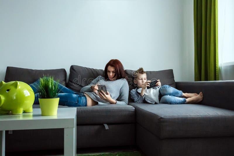 Den moderna familjen, alla sitter i smartphones än passionerade Begreppet av harmfulness av moderna grejer, arkivfoto