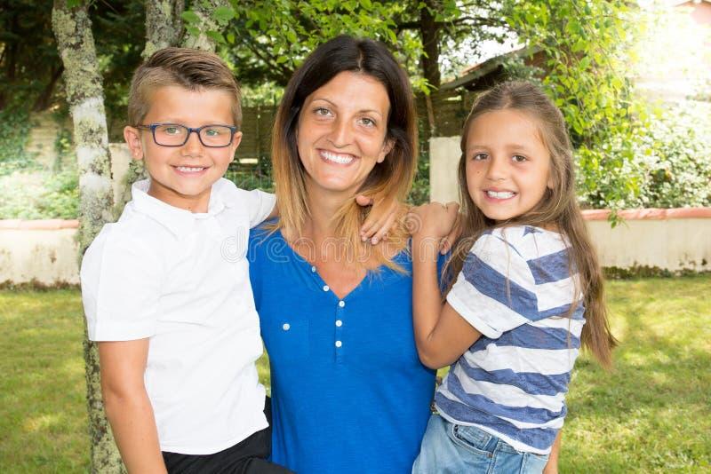Den moderna familjensamstående mammaföräldern med två barn dotter och son i armar i hem- hus arbeta i trädgården arkivbild