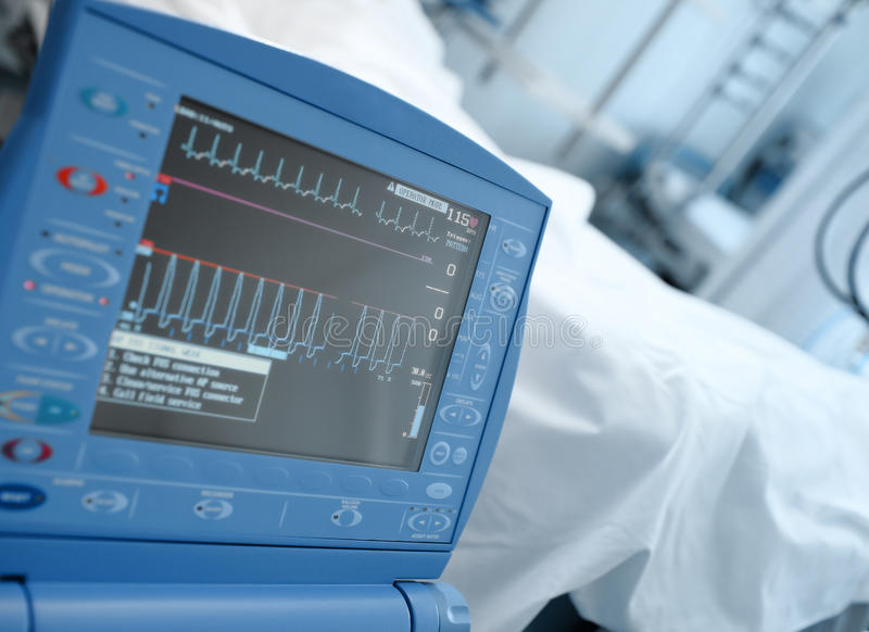 Den moderna ICU-bildskärmen i kliniskt avvärjer bredvid sängen av patien arkivbilder