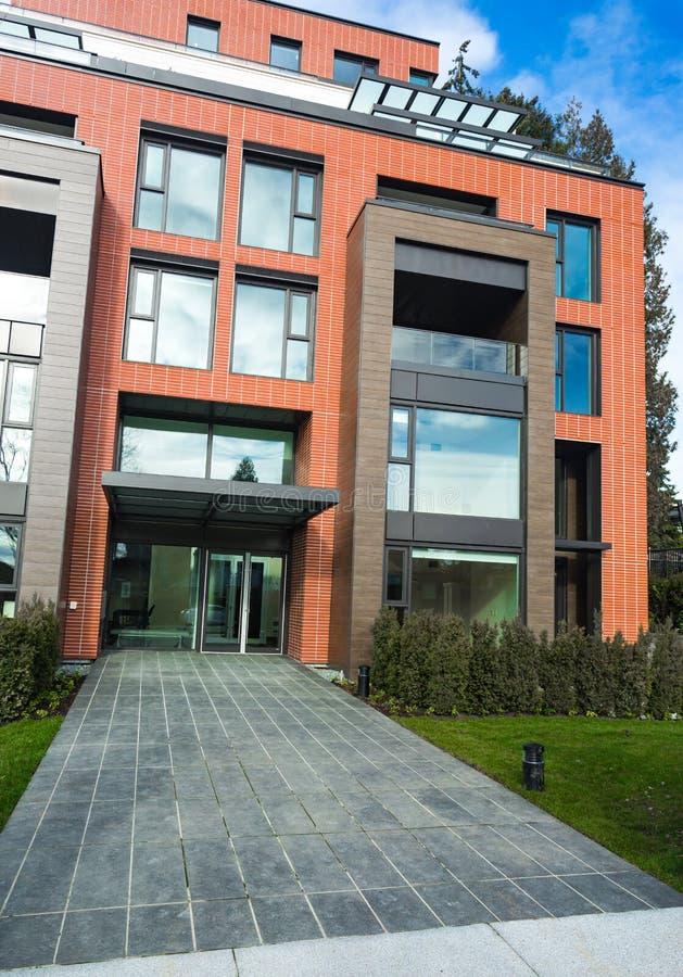 Den moderna lägenhetskomplexet för röd tegelsten med heltäckande vaggar staketväggen Hem- komplex fastighet för bostads- byggnade arkivbilder