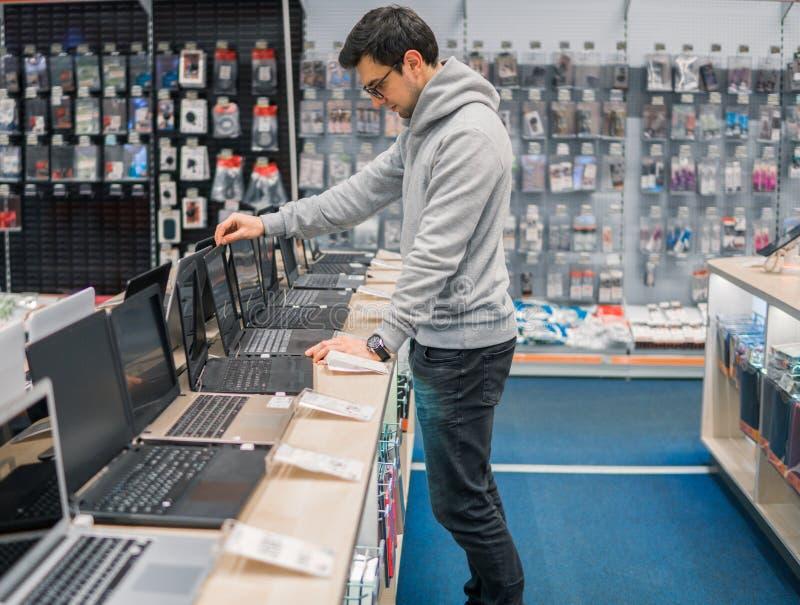 Den moderna manliga kunden som väljer bärbara datorn i datoren, shoppar royaltyfri fotografi