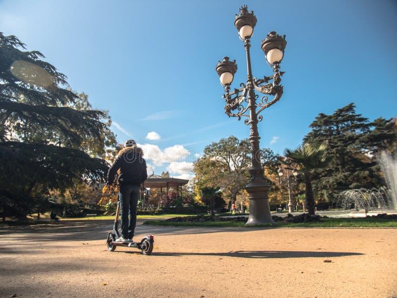 Den moderna mannen med hjälmen som använder den elektriska sparkcykeln i soligt, parkerar 1 arkivfoto