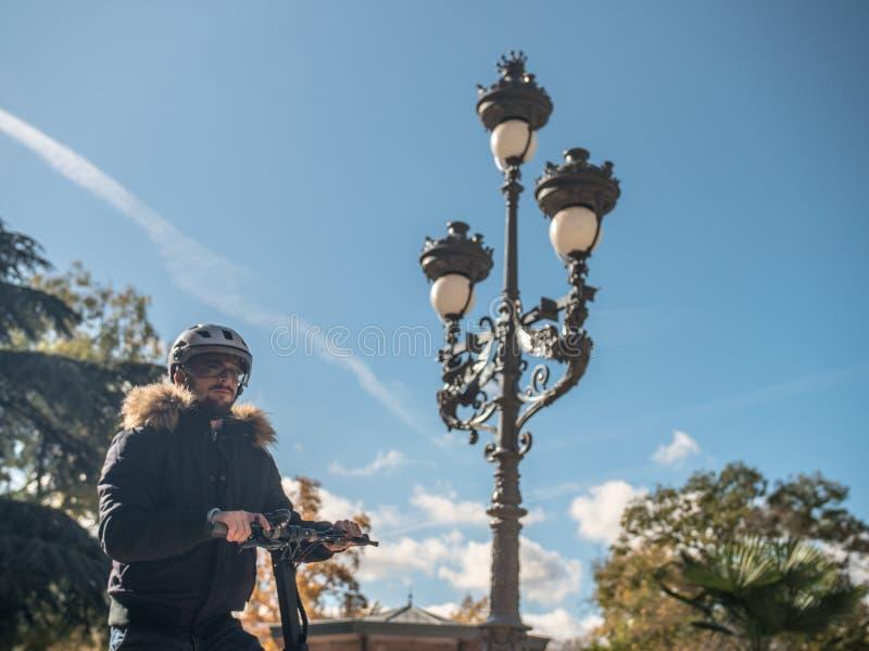 Den moderna mannen med hjälmen som använder den elektriska sparkcykeln i soligt, parkerar 7 arkivfoton