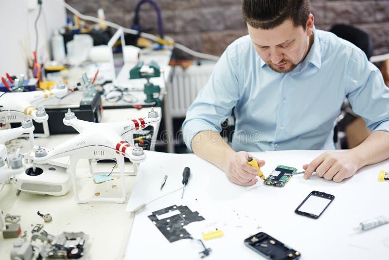 Den moderna mannen som arbetar i elektronikservice, shoppar arkivfoton
