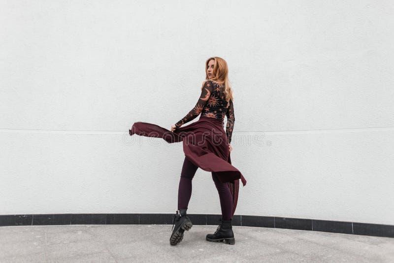 Den moderna n?tta unga kvinnan i en trendig m?nstrad blus i moderiktiga purpurf?rgade fl?sanden i svarta skor f?r tappning med en arkivbilder