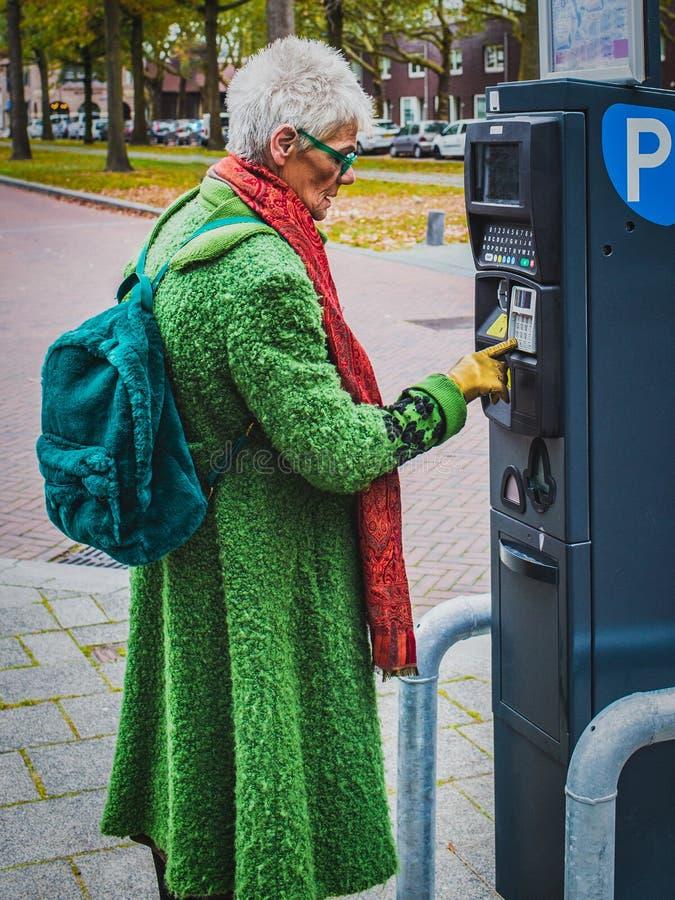 Den moderna staden för äldre kvinna betalar att parkera arkivbilder