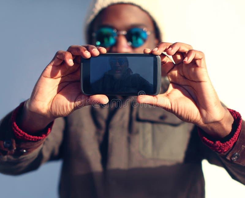 Den moderna stilfulla afrikanska mannen gör selfie, främre sikt för skärm royaltyfri bild