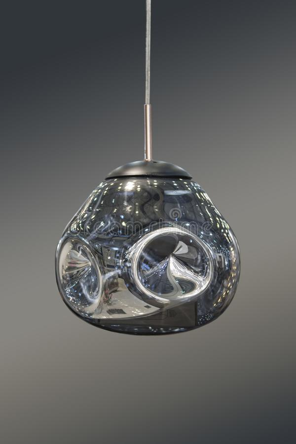 Den moderna strömlinjeformade spegeln försilvrar ljuskronan Metall formad hängelampa som intresserar den isolerade formen på grå  arkivfoton