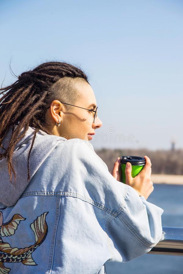 Den moderna trendiga härliga flickan bara på en vår går vid floden fotografering för bildbyråer