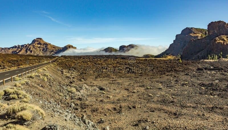 Den moderna vägen, körningar längs strömmarna av djupfryst lava och som omger av bergvegetation, vilar på molnen som flödar in i arkivfoto