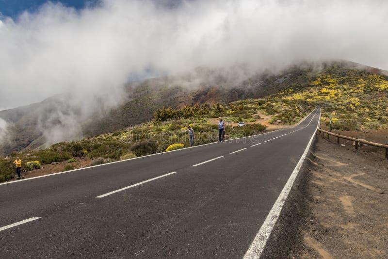 Den moderna vägen, körningar längs strömmarna av djupfryst lava och som omger av bergvegetation, vilar på molnen som flödar in i arkivfoton