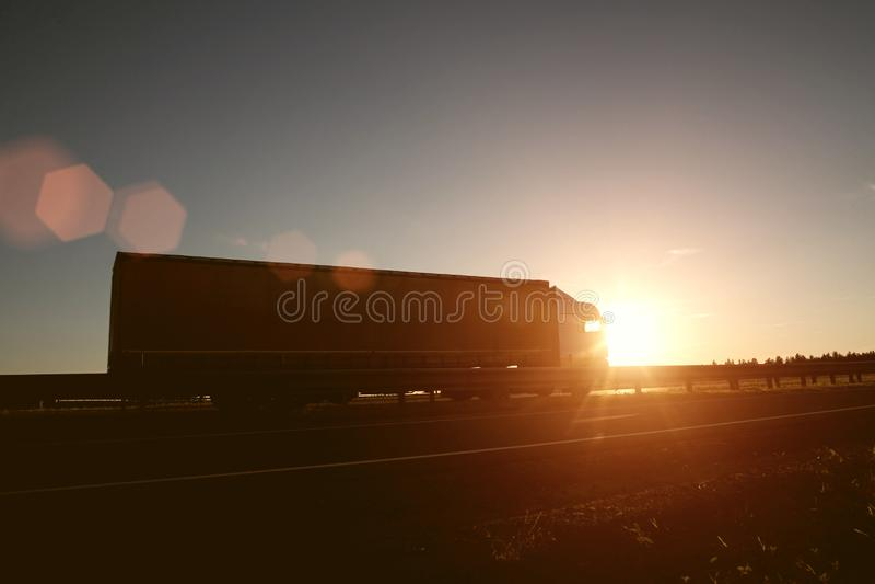 Den moderna vagnlastbilen transporterar last mot bakgrunden av en solnedgång Begreppet av lastbilsförare i fältet av frakter och royaltyfri fotografi